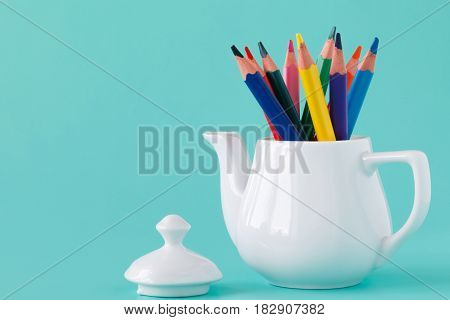 A Group Of Color Pencils In A White Kettle On An Isolated Background