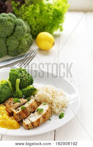fried chicken breast fillet with fruity mango chuntey broccoli and rice and the ingredients on a white painted wooden kitchen table vertical selected focus and narrow depth of field