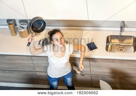Mad and crazy housewife woman with kitchen pan. top view. looking at camera.