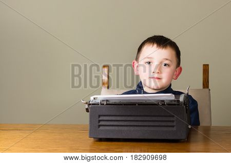 Cute little boy looks distracted while working with an old vintage black typewriter at home