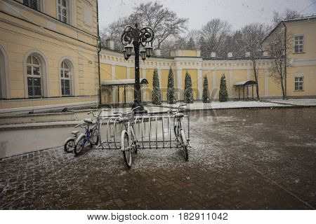 Scenic view of bicycles covered with fresh snow after weather phenomena - snowfall in late April near Moscow