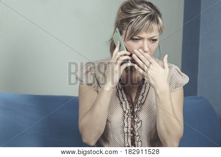 Young woman getting bad news by phone.