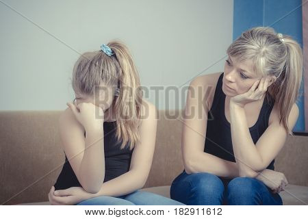Teenager problems - Sad crying teenage girl and her worried mother.