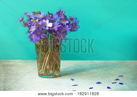 Bouquets of purple spring violet in glass near the window.
