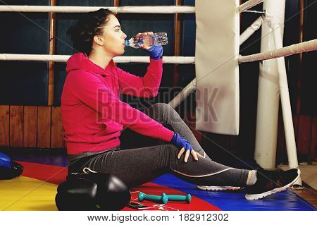 Beautiful Thirsty Boxing Girl Drinking Water In The Ring. Training At The Gym. Sporty Female Doing B