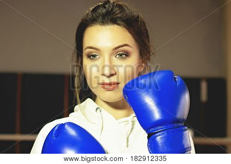 Portrait Of Beautiful Boxing Girl Posing With Blue Boxing Gloves. Training At The Gym. Sporty Female