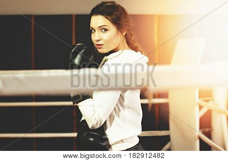 Portrait Of Beautiful Boxing Girl In Black Gloves Posing In The Ring. Training At The Gym. Sporty Fe