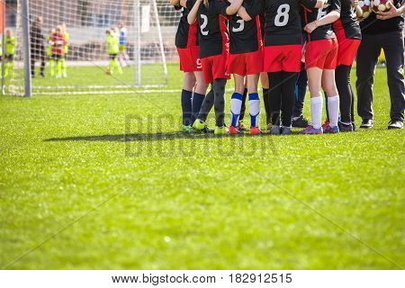 Children's Football Team on the Pitch. Girls in Black and Red Soccer Kits Standing Together on the Football Field. Motivated Young Soccer Players with Coach Talking Before the Final Game of School Tournament