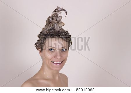 Young woman washing her head in the shower by shampoo.
