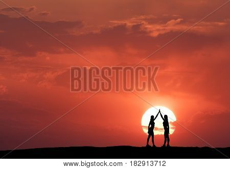 Silhouette of a standing young sporty girls with raised up arms on the hill on the background of sun and red sky with clouds. Landscape with women holding hands at colorful sunset. Lifestyle