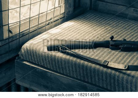 Daylight through barred window onto wooden stock of well used rifle on green and white striped cover of bed in hunters shed split tones old effect.