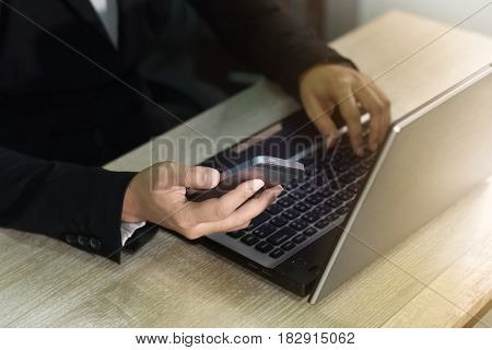 A woman's hand working on a laptop computer and interactive technology online on a smartphone.