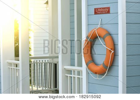 Orange lifebuoy All Water rescue emergency equipment. It hanging on blue wall
