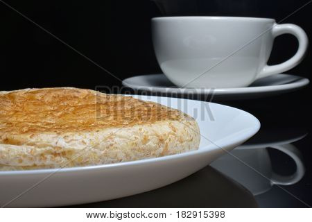 Close-up whole wheat bread on white dish and blur coffee cup.