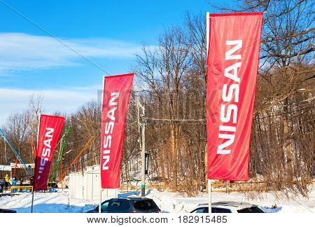 SAMARA RUSSIA - FEBRUARY 14 2016: Dealership flags Nissan over blue sky in sunny day. Nissan is a Japanese multinational automaker