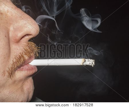 the man smoking cigarette on black background