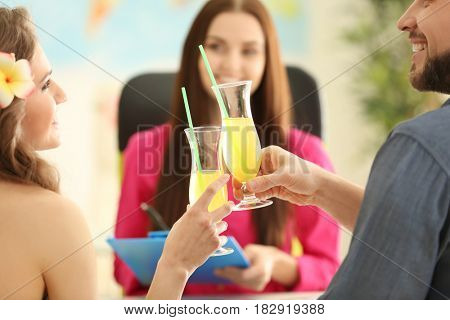 Adventure concept. Young couple drinking cocktails while visiting travel agency