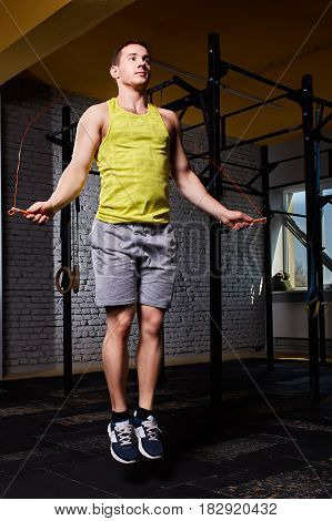 Young athletic sportsman in the sportwear working with jumping rope in cross fit gym against brick wall. Woman in the yellow t-shirt, shorts and sportive shoes. Healthy lifestyle. Vertical photo.