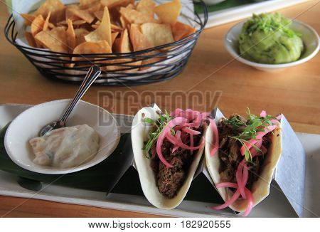Pulled pork tacos, with dressing and tortilla chips on the side