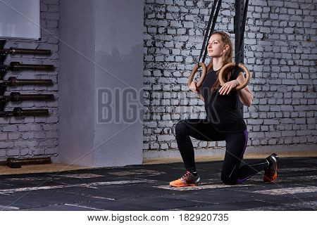 Young fit woman in the sportwear doing pull-ups on gymnastic rings against brick wall in the cross fit gym. Sporty woman in the black t-shirt, leggings and sportive shoes. Portrait of beautiful sporty woman. Healthy lifestyle.
