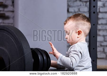 Close-up photo of little boy with barbell against brick wall in the cross fit gym. Cute child in the grey sportwear. Detail of the little boy. Rearing child in the healthy lifestyle.