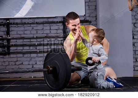 Portrait of happy father and son with barbell in the cross fit gym against brick wall. Father and little cute boy in the sportwear and sportive shoes. Horizontal photo. Rearing child in the healthy lifestyle.