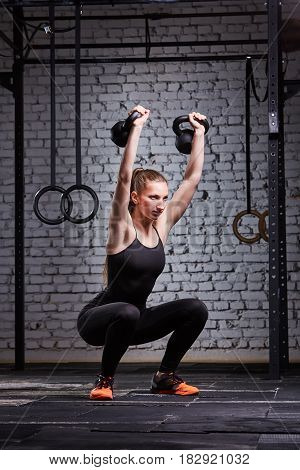 Young fitness woman exercising cross fit with kettlebell against brick wall in the gym. Sporty woman in the black sportwear, t-shirt, legginga and sportive shoes. Healthy lifestyle. Concept of cross fit activity.