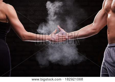 Cropped image of hands of athlete muscular man and woman against dark background. Sportwer, shorts, t-shirt and leggings. Body, muscle and abs. Concept of the cross fit activity in couple.
