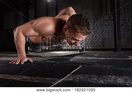 Portrait of a young handsome sportsman doing push ups exercise with one hand against brick wall in fitness gym. Man in the sportwear. Body, muscle and abs. Healthy lifestyle. Close-up photo.