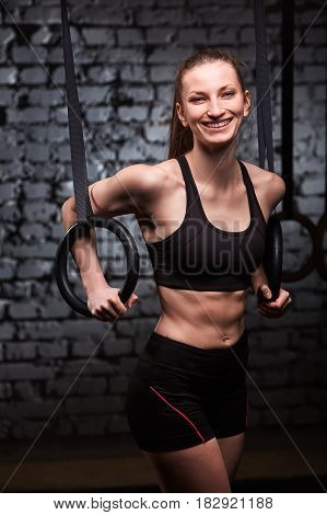 Fit young sporty woman holding gymnast rings and smiling at the cross fit gym against brick wall. Sporty woman in the black sportwera, t-shirt and shorts. Portrait of beautiful woman. Healthy lifestyle.
