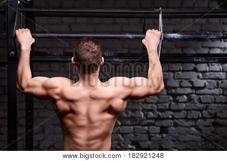 Rear view photo of muscular male doing exercises on horizontal bar against brick wall at the cross fit gym. Body and muscle. Power and energy. Healthy lifestyle.