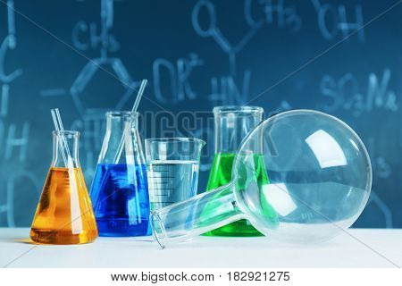 Test beakers and flasks on blackboard background