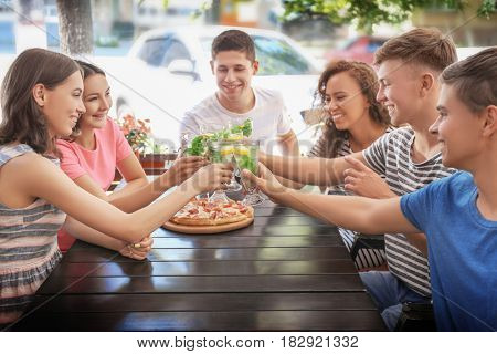 Happy friends eating pizza in cafe
