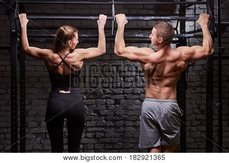 Rear view photo of muscular man and woman doing exercises on horizontal bar against brick wall at the cross fit gym. Sporty couple in the sportwear. Power and energy. Healthy lifestyle. Concept of the cross fit activity in the couple.