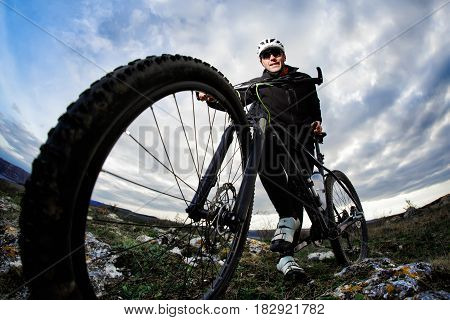 Bottom view photo of cyclist in the black sportwear standing with his bike on the rock against blue sky with clouds. Sportsman in the helmet and sunglasses. Extreme travel in the countryside. Summer season. Healthy lifestyle. Fisheye.