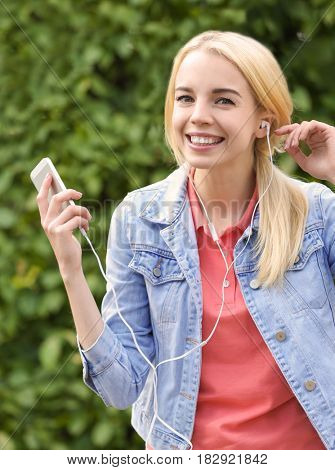 Young beautiful woman with earphones listening to music