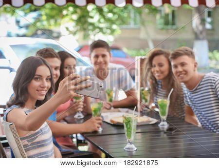 Happy friends taking selfie in cafe