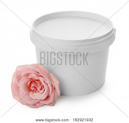 Plastic bucket with sugaring paste and flower on white background