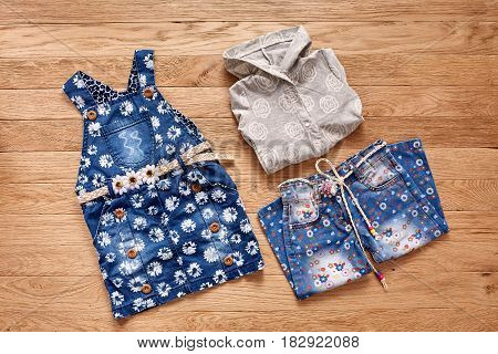 Children's jeans, jacket and denim dress on wooden background. White jacket with hood, blue jeans in flowers and denim dress in flowers with cute belt. Clothes for little girl. Casual and modern chidren's style.