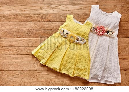 Two beautiful dress for little girls on wooden background. Cute white and yellow small dress with flowers on the belt. Clothes for little girl. Elegance chidren's style. Concept of the children's fashion industry.