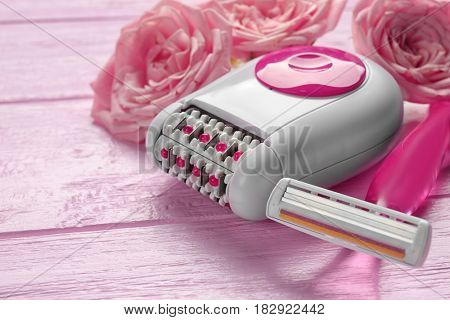 Epilator and razor on color wooden background, closeup
