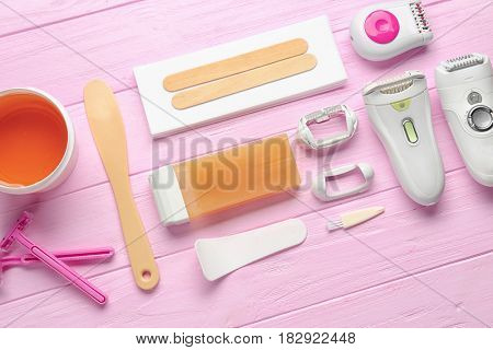 Set for hair removal on wooden background