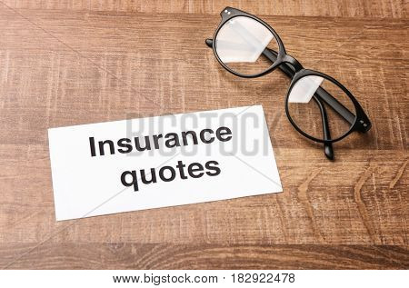 Card with text INSURANCE QUOTES and glasses on wooden background