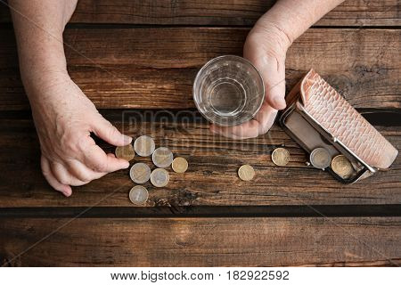 Senior woman's hands with glass of water, purse and coins on wooden background. Poverty concept