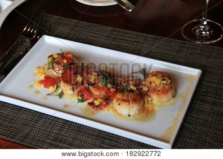 Long white dish with grilled sea scallops and corn with creamy sauce and relish