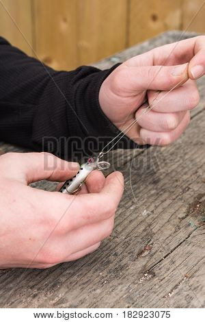 male hands tying a fishing lure to mono filament fishing line on a picnic table.