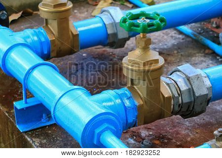 water valve plumbing joint steel tap pipe with green knob close up