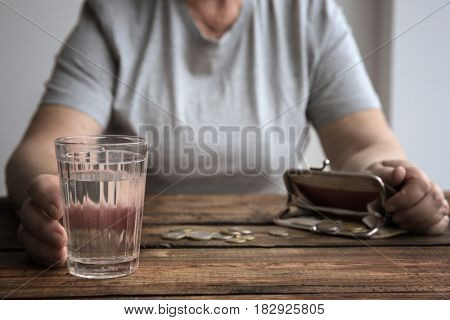 Senior woman sitting at table with glass of water, purse and coins, closeup. Poverty concept