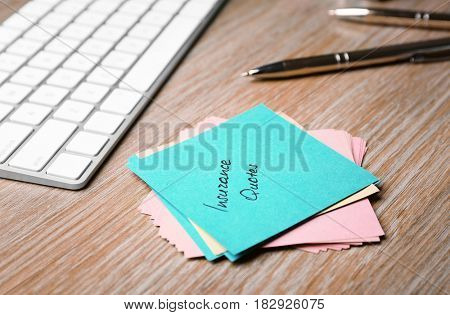 Paper note with text INSURANCE QUOTES and keyboard on wooden background
