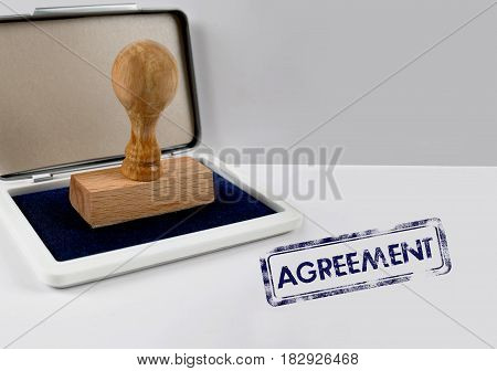 Wooden stamp on a white desk AGREEMENT